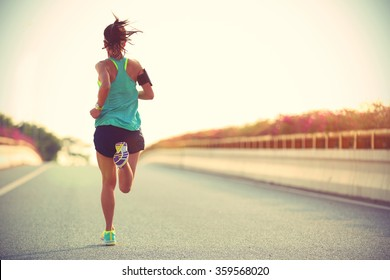 Photo of Young woman runner running on city bridge road