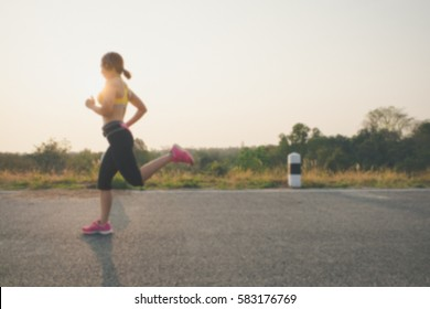 young woman runner running on road, sunrise light ,Blur