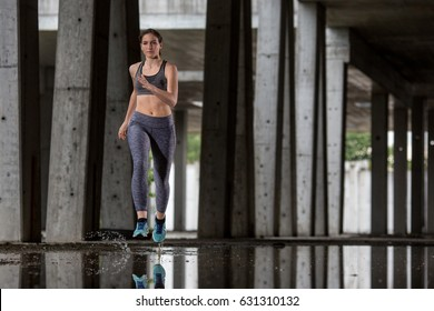 Young woman runner is seen running in an abandoned hall. Running is a good exercise for cardio vascular system and general health and weight control.