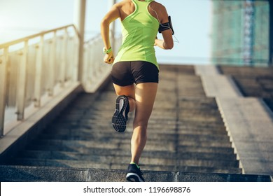 Young woman runner sportswoman running up city stairs jogging and running in urban training workout