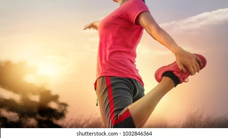 Young woman runner stretching legs before running at sunset rural trail.
