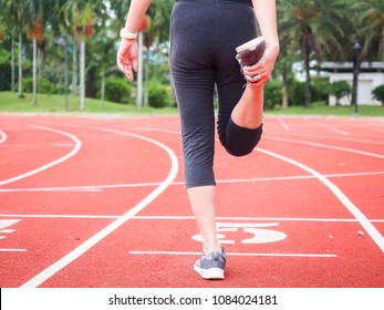 Young woman runner stretching legs before running race on race track. Sport concept.