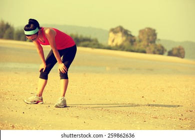 young woman runner taking a breack after running hard at beach