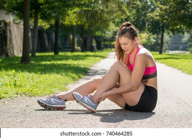 a young woman  runner touching foot in pain outdoors