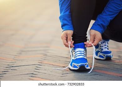 Young woman runner tying shoelace before run