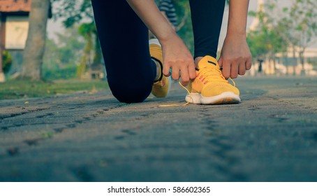 young woman runner tying shoelaces outdoor
