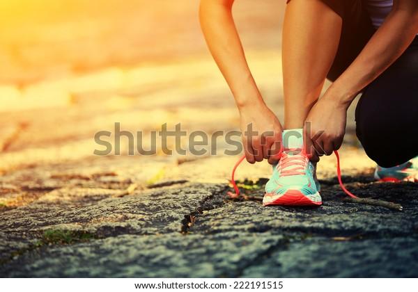 靴ひもを結ぶ若い女性のランナー