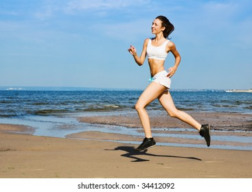 Young woman running alone on the beach