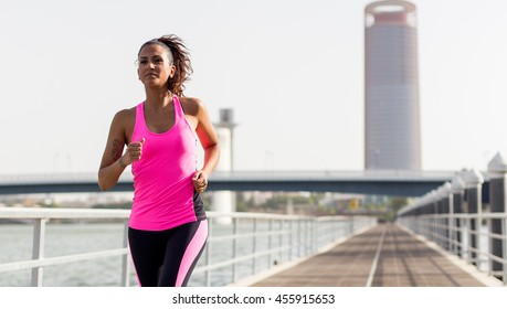 Young woman running along a river