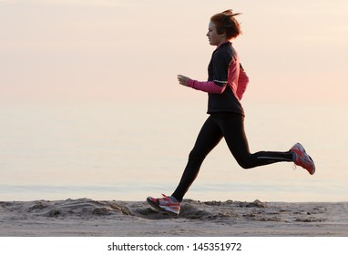 Young woman running along the waterfront
