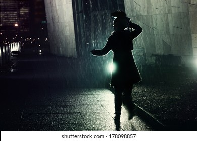 young woman running away from the rain at night, protecting her head with her bag
