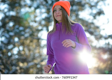 Young Woman Running in the Beautiful Winter Forest at Sunny Frosty Day. Active Lifestyle Concept.