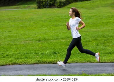 Young woman running in city park