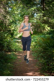 Young Woman Running Down Trail