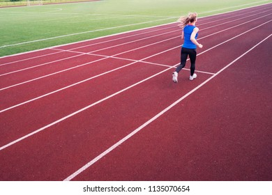 Young woman running during sunny evening on stadium track. A blonde in a blue t-shirt and black leggings runs across the stadium.