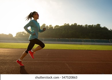 Young woman running during sunny morning on stadium track