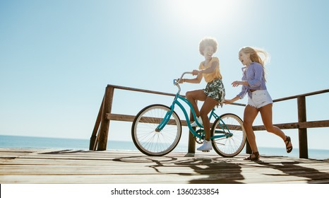 Young woman running with her friend riding a bike on boardwalk. Two friends enjoying their summer vacation a the beach.