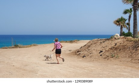 Young woman running with her white dog on the Mediterranean coastline path in a beautiful sunny day near the Kapparis beach, Paralimni, Cyprus.