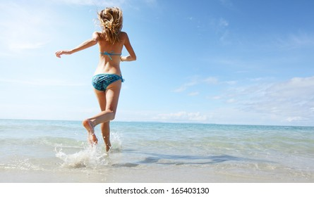 Young woman running into tropical sea on the beach at sunny day