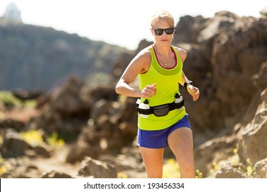 Young woman running in mountains on sunny summer day. Beauty female runner jogging and exercising outdoors in nature, rocky trail footpath on La Palma, Canary Islands