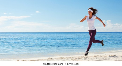 Young woman running on the beach. Summer concept. Healthy lifestyle. White sand, blue sky and crystal sea of tropical beach. Vacation at Paradise. Ocean beach relax, travel