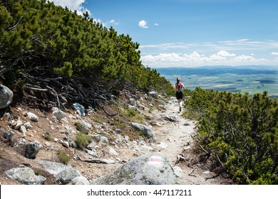 young woman running on the high mountain trail with beautiful sky and clouds view
