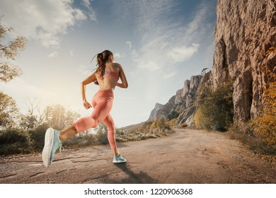 Young woman running on a mountain road in the beautiful nature. Girl runner in sneakers jogging workout outdoors. Weight loss concept. Healthy lifestyle. Fitness on outdoors.