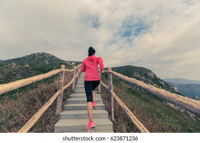 young woman running on mountain stairs