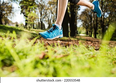 Young woman running on a road during day in the park in autumn. Selective focus. Low depth of field. Detail of sport feet on trail.