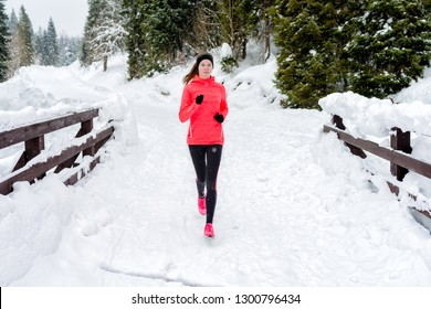 Young woman running on snow in winter mountains wearing warm clothing gloves in snow weather. Sport, fitness inspiration and motivation. Happy teen woman trail running. Female runner jogging outdoors