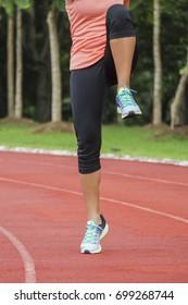 Young woman running on stadium track. Portrait running girl.
