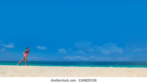 Young woman running on summer beach on the coast of the ocean blue sky background