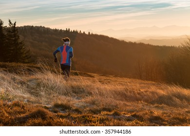 young woman running on the trail in the cold morning in mountains with sunrise