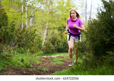 Young woman running on a trail running track, healthy lifestyle and sport concepts.