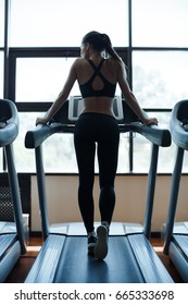 Young woman running on treadmill. Beautiful young woman in gym. Running in sport club
