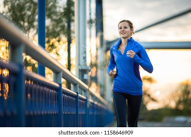 Young woman running outdoors, in a city, over a bridge