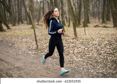 Young woman running outdoors in a city park on early spring day