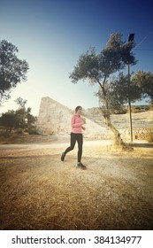 Young woman running outdoors on a lovely sunny summer day in for