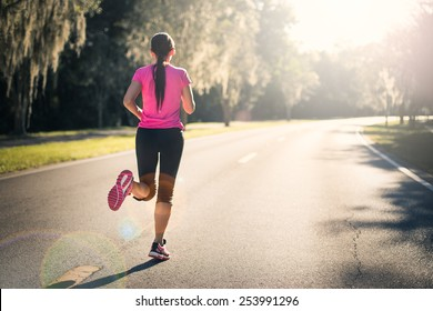 Young woman running outdoors at sunrise or sunset. Wellness and health concept.