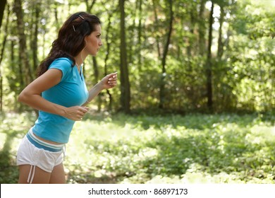 Young woman running in the park listening to music