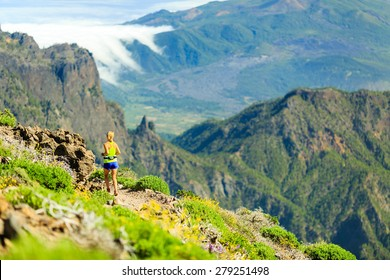 Young woman running or power walking in mountains on sunny summer day. Beautiful natural landscape and female runner jogging exercising outdoors in nature, rocky trail footpath on Canary Islands