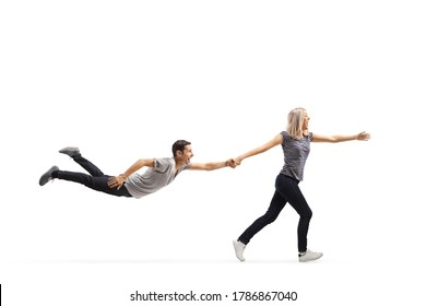 Young woman running and pulling a young man by the hand who is floating in air isolated on white background - Shutterstock ID 1786867040