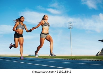 Young woman running a relay race and giving relay baton to her teammate. Female runner passing the relay baton during race.