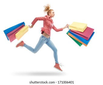 young woman running with shopping bags in hands