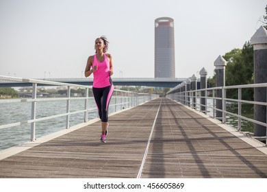 Young woman running with skyscraper behind