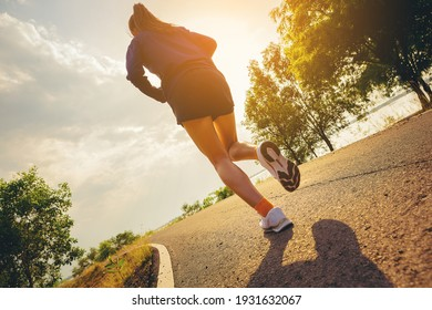 Young woman running sprinting on road. Fit runner fitness runner during outdoor workout with sunset background.