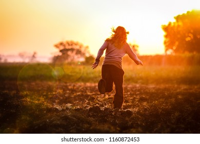 Young woman is running to the sunrise