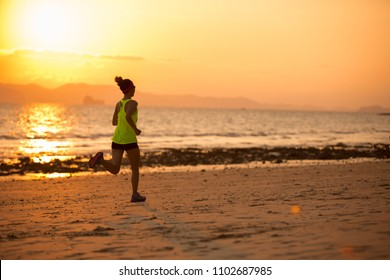 Young woman running at sunset sandy beach