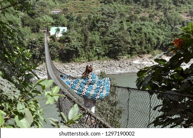 Young woman running through the bridge over the river. Asia, Nepal