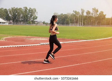 Young woman running in track stadium